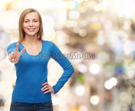 smiling teenage girl showing v sign