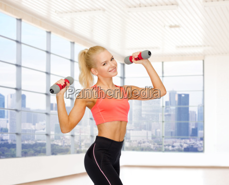 smiling woman with dumbbells flexing biceps