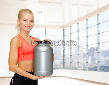 smiling spory woman holding protein jar