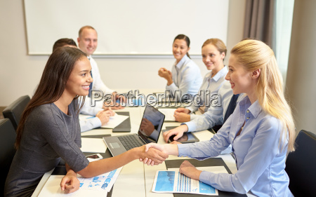 smiling business people shaking hands in