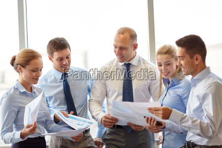 happy business people with papers talkig