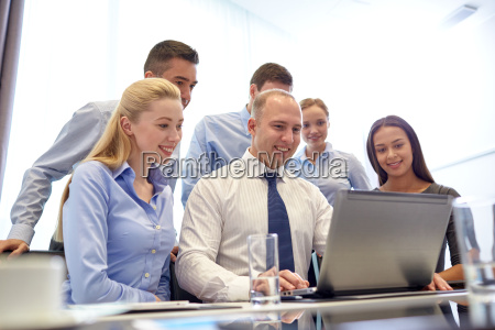 smiling business people with laptop in