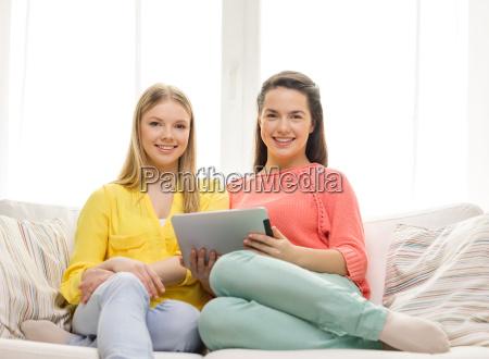 zwei laechelnde teenager maedchen mit tablet