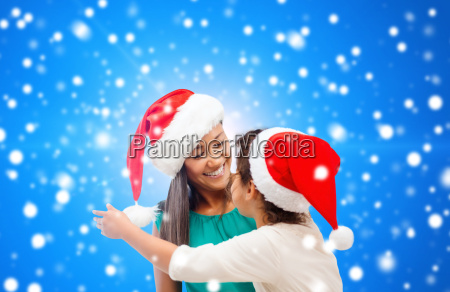 happy mother and girl in santa