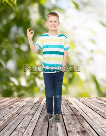 smiling little boy showing ok sign