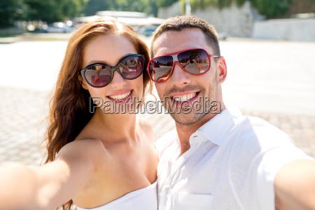 laechelnd paar mit sonnenbrille machen selfie