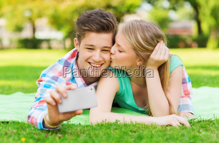 smiling couple making selfie and kissing