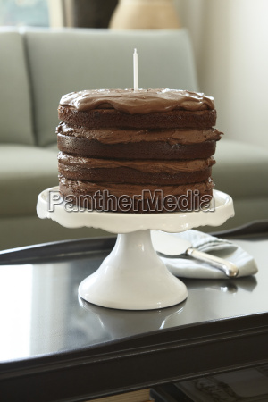 layered chocolate birthday cake with candle