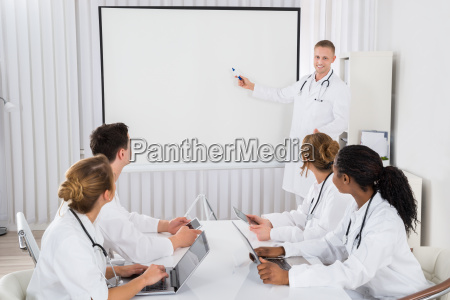 doctor pointing at board in front
