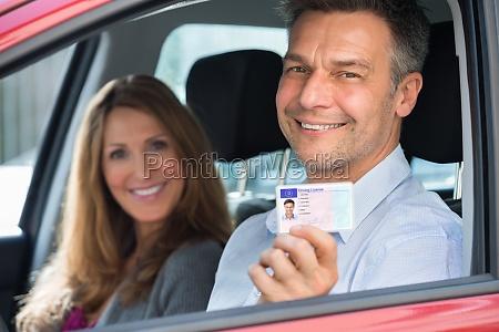 man sitzt im auto angezeigt fuehrerschein