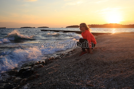 girl sits on the shore