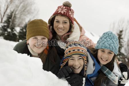 winterschnee vier kinder gruppiertenlachend durch eine