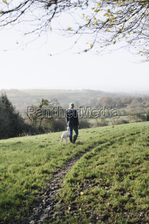a woman walking with a dog