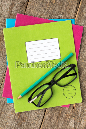colored exercise books pencil and glasses