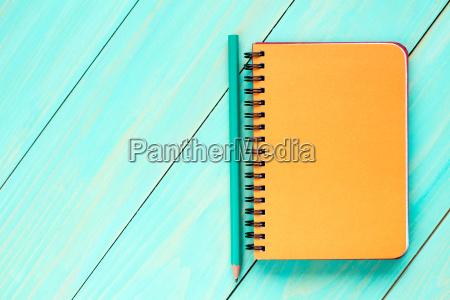 orange notebook with pencil