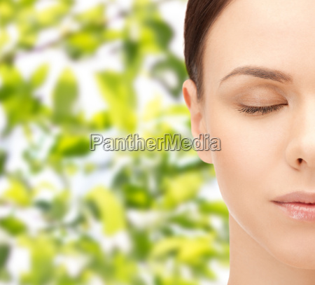 young woman face over green leaves