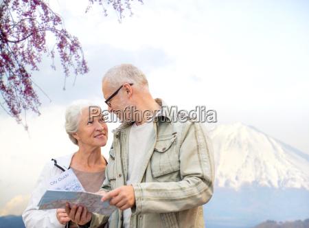 glueckliches seniorenpaar mit reiseplan ueber berge