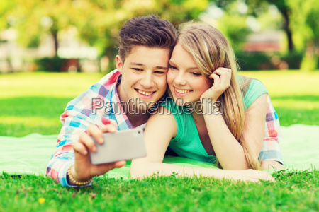 smiling couple making selfie in park