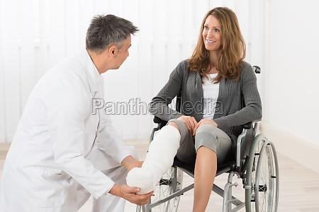 physiotherapeut untersucht bein des patienten