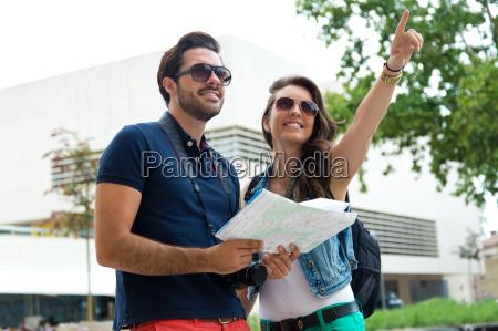 junges touristenpaar nutzt ihre karte und