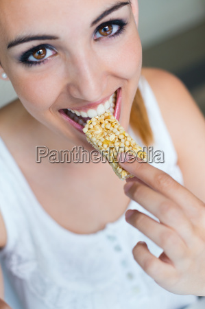 frau isst muesli bar snack