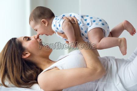 mutter und baby spielen und laechelnd