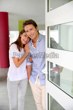 cheerful couple inviting people to enter