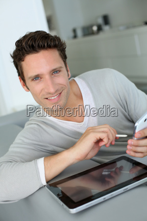 man in sofa using tablet and