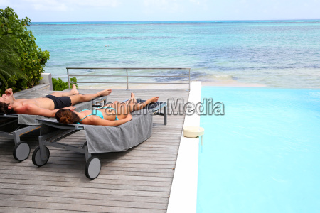 couple relaxing in long chairs in