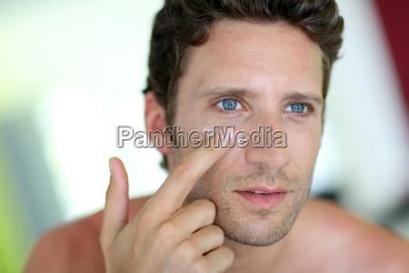 handsome man applying moisturizing cream
