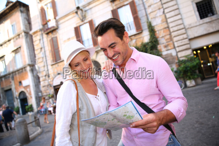 smiling couple reading city map in