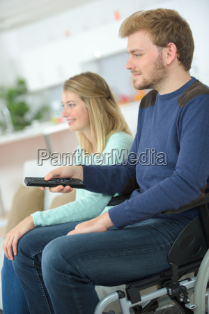 disabled man watching tv with his