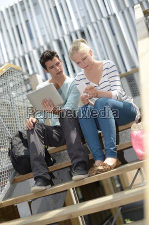 students in school yard using digital