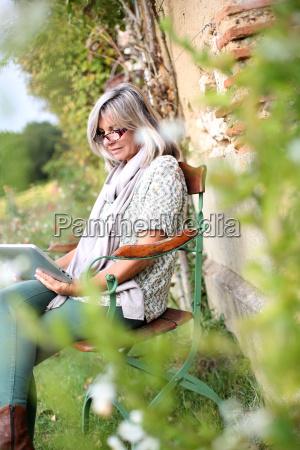 senior woman using digital tablet in