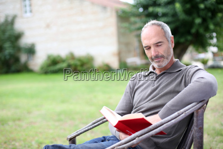 senior man reading novel in country