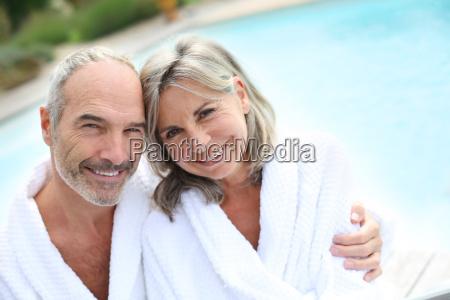 glueckliche aeltere paare im bademantel durch
