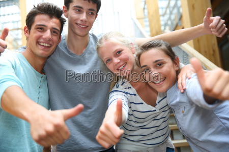 group of cheerful students showing thumbs