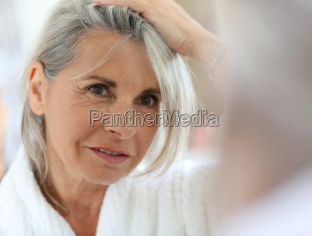 aeltere frau gesorgt durch graue haare