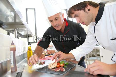 chef hilft schueler im catering foie