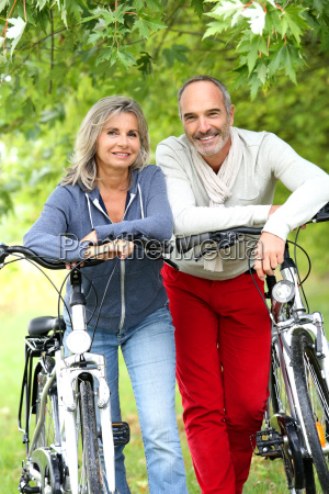 cheerful senior couple with bicycle in
