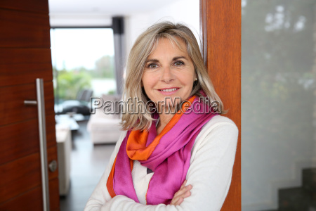 cheerful senior woman standing at home
