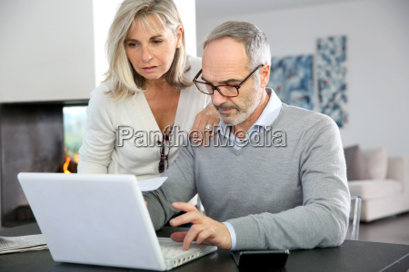 senior couple at home using internet