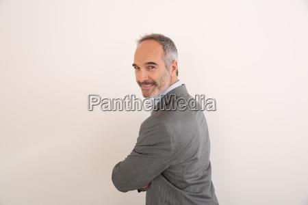 cheerful senior businessman standing on white