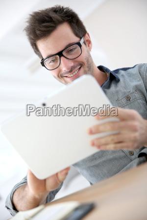 mann mit brille mit touchpad websurfing