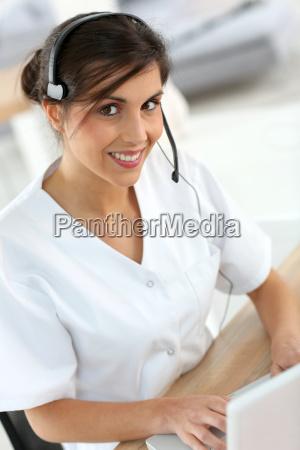 portrait of medical secretary typing report