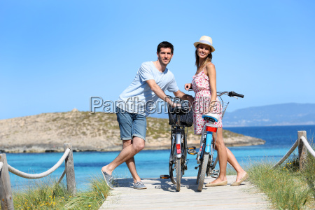 couple standing by gorgeous beach with