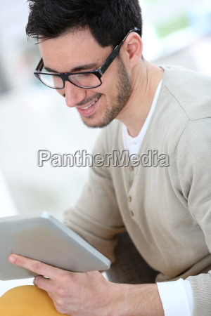 young man with eyeglasses websurfing with