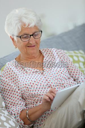 elderly woman using digital tablet at