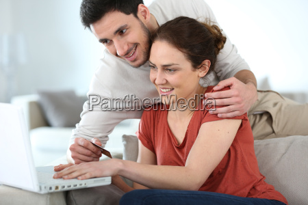 couple at home shopping online with