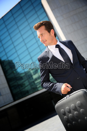 businessman walking with briefcase outside modern